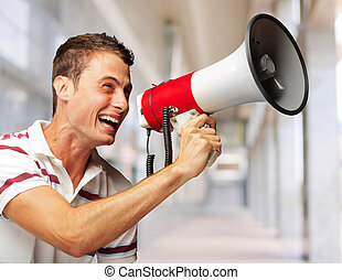 Portrait Of A Handsome Young Man Shouting With Megaphone -...