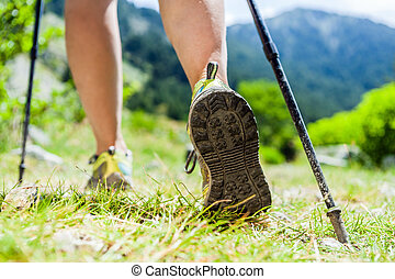 Nordic walking legs in mountains - Woman hiking in...