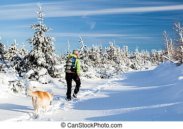 Winter hiking with dog, woman hiker