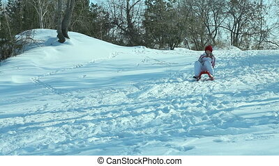 Tobogganing - Cheerful girl tobogganing down the hill and...