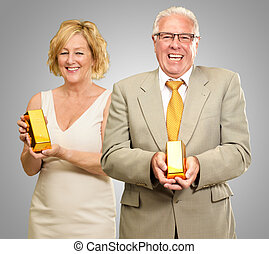 Two Senior Couple Holding Goldbar On Gray Background