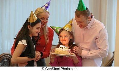 Family birthday party - Happy family blowing candles at...