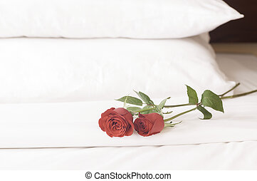 Romantic getaway with roses on bed