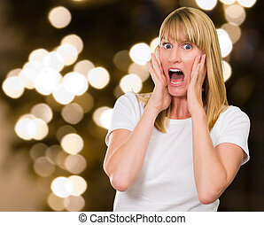 Portrait Of Shocked Woman against a blurry golden background