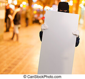 Portrait of a man wearing mask holding blank card - Man...