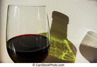 red wine bottle and glass - the shadow of a wine bottle and...