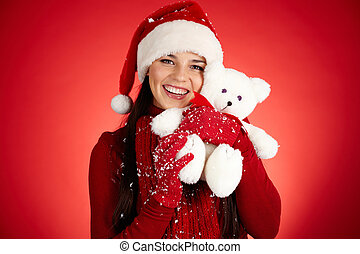 Merriment - Joyful girl in Santa cap with white teddy bear...