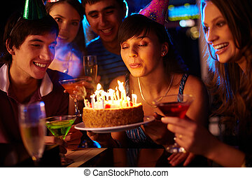 Making a wish - Portrait of charming girl blowing on candles...