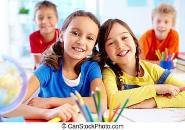 Diligent pupils - Portrait of two diligent girls looking at...