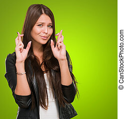 Young Woman With Crossed Fingers against a green background