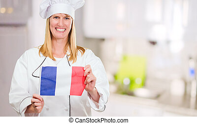 Happy Chef Holding French Flag in a kitchen