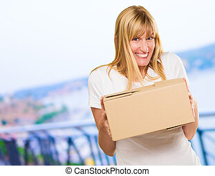 Woman Holding Cardboard box, outdoor