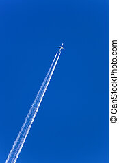 contrails - a plane with contrails in the blue sky. smog and...