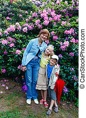 Family near blossoming Rhododendron bush.