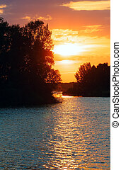 Sunset and lake. - Pink-yellow sunset and sun reflection on...
