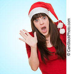 surprised woman wearing a christmas hat against a blue...