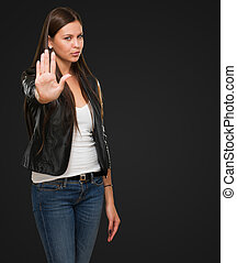 Young Woman Showing Stop Hand Gesture against a black...