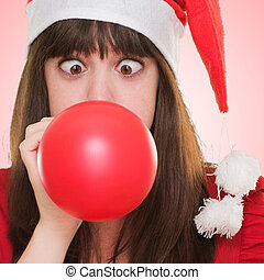 christmas woman blowing a balloon with her eyes crossed...