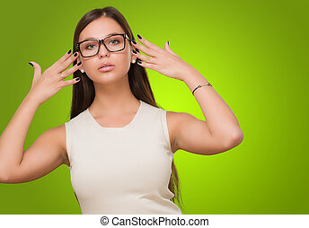Beautiful Young Woman With Eye Glasses against a green...