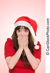 surprised christmas woman covering her mouth against a red...