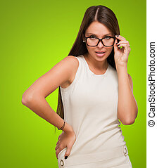 Sexy woman with glasses posing against a green background