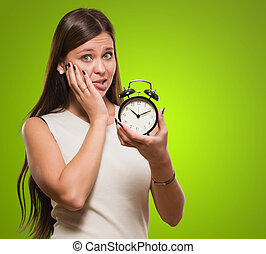 Worried Woman Holding Alarm Clock against a green background