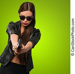 Woman Aiming With Gun against a green background
