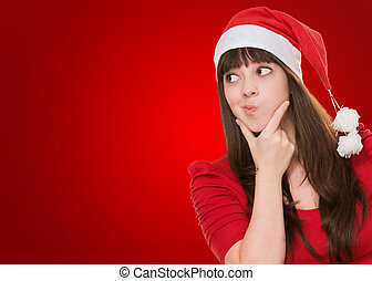 woman thinking and wearing a christmas hat against a red...