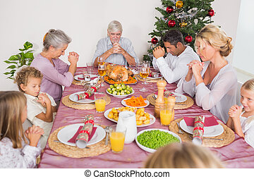 Family saying grace before christmas dinner