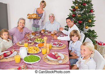Mother bringing turkey to dinner table