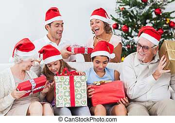 Excited family exchanging gifts at christmas