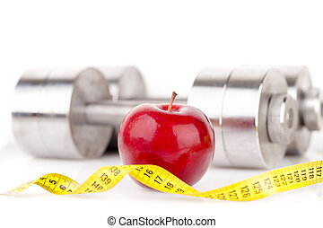 Dumbbell and an apple - Dumbbell with an apple isolated on a...