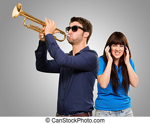 Man Blowing Trumpet In Front Of Frustrated Woman On Gray...