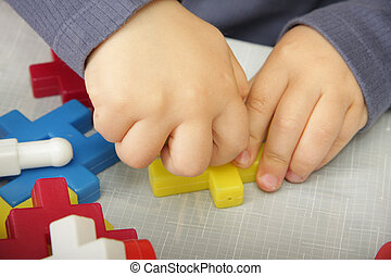 Hand fixing meccano - Child hands playing with colored toy...