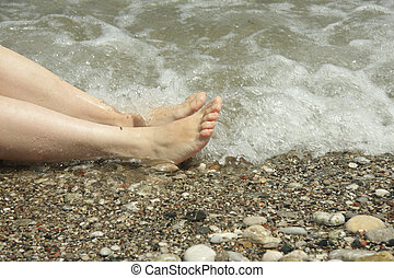 Feets in white caps - Woman feets laying in a sea water...