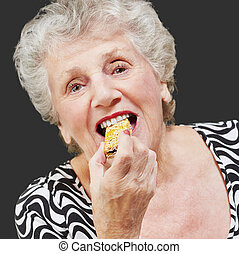 Portrait of a woman eating granola bar on black background