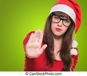 christmas woman doing a stop gesture against a green...