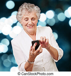 Senior woman using cellphone, illuminated