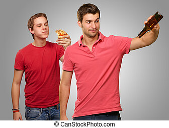 Young Man Holding Empty Bottle And Other Man Having Pizza On...
