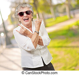 Senior woman wearing sunglasses doing funky action, outdoor