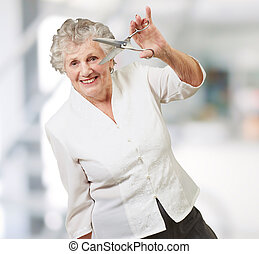 Senior woman holding scissors, indoor