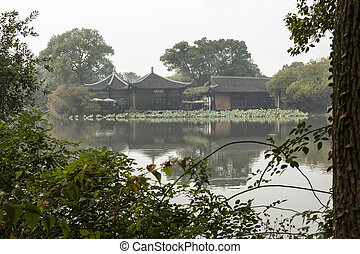 Temples on West Lake - Large temple seen through trees on...