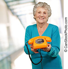Mature Happy Woman Holding Telephone, Indoor