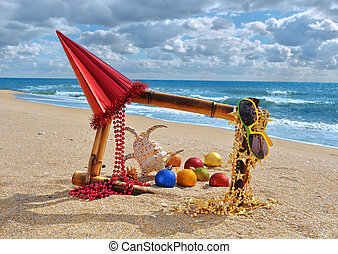 Bamboo frame with christmas decorations on the beach -...