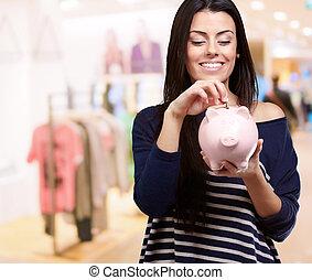 Happy Young Woman Holding Piggybank, Indoor