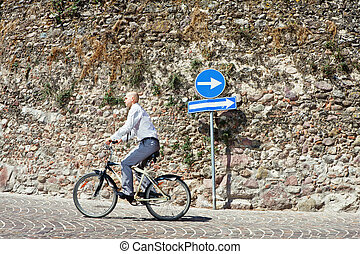 Going the Wrong direction - Businessman going on bicycle the...