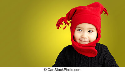 Portrait Of Baby Boy Wearing Warm Clothing against a yellow...
