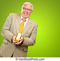 Senior Man Holding Gold Bar On Green Background