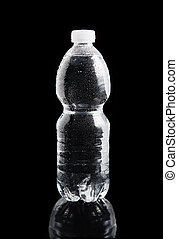 Plastic bottle of water with a drops on it on a black...