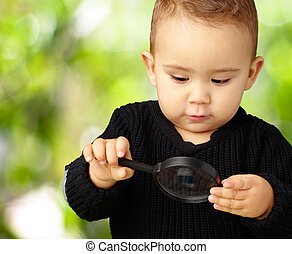 Baby Boy looking at Magnifying Glass against a nature...